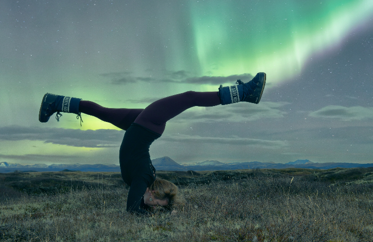yoga teacher emma henry doing forearm stand under the northern lights on our iceland yoga retreat