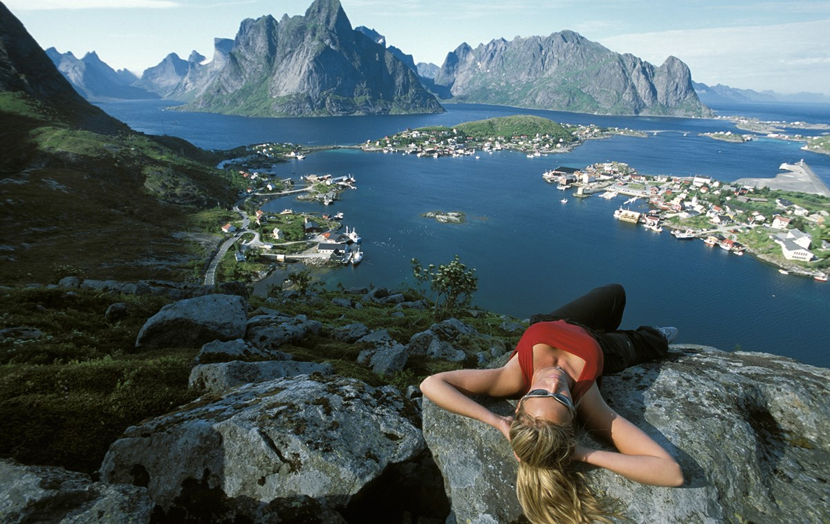 woman resting at the top of a mountain in norway on one of our best yoga retreats for hiking