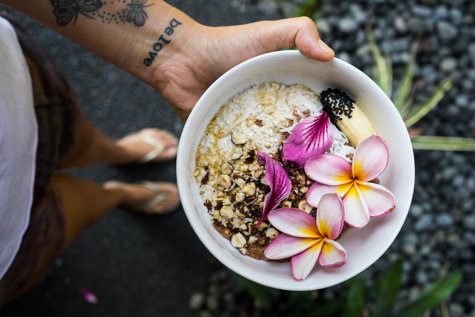 bowl of healthy porridge with nuts and flower toppings outside in tropical setting