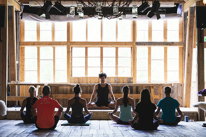 meditation yoga teacher on yoga retreat big hall large windows
